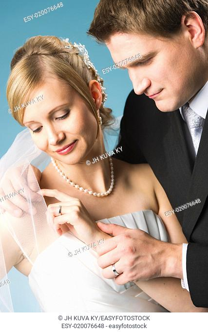 Bride and groom watching rings, blue background, vertical format