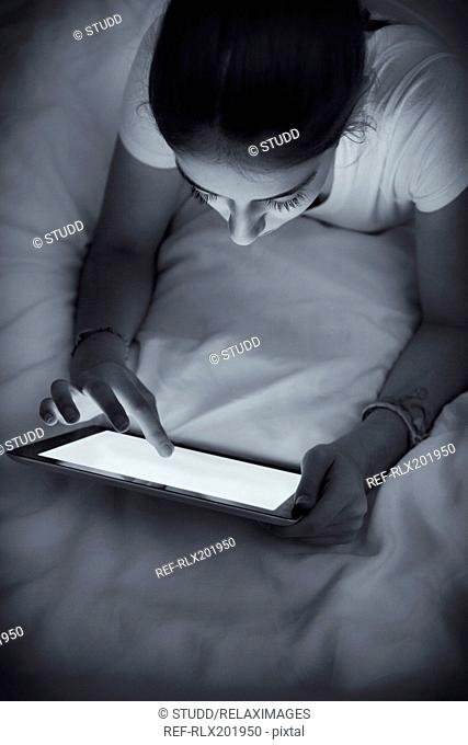 Teenage girl using tablet PC in bed at home