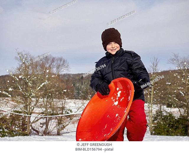 Caucasian boy holding sled on snowy hill