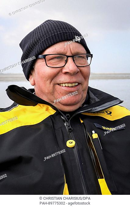 Mailman Michael Stobbe sits on a mud flat carriage of the postal service on Neuwerk island, Germany, 4 April 2017. For 20 years