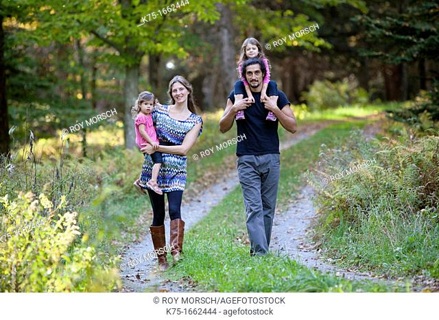 Family of four walking down country road