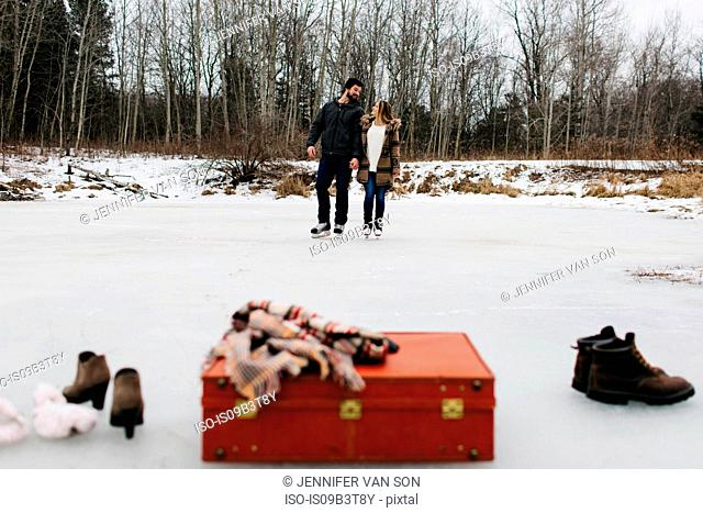 Red suitcase, boots, shawl, couple skating in background, Whitby, Ontario, Canada