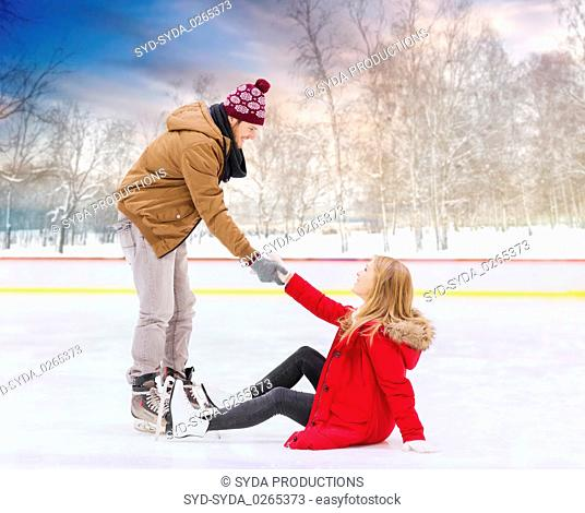 man helping woman to get up from skating rink