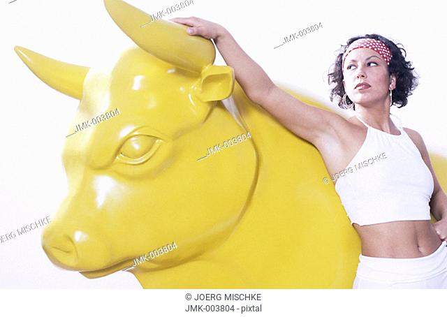 Studio picture of a young woman, 15-20 20-25  25-30 years old, standing beside a yellow bull