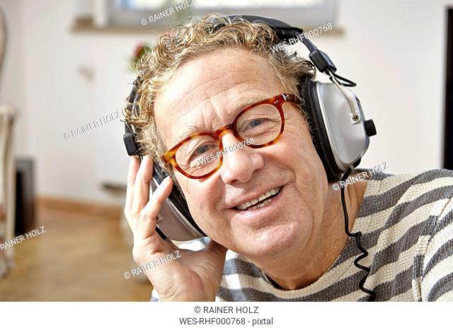 Senior man wearing headphones, listening to music