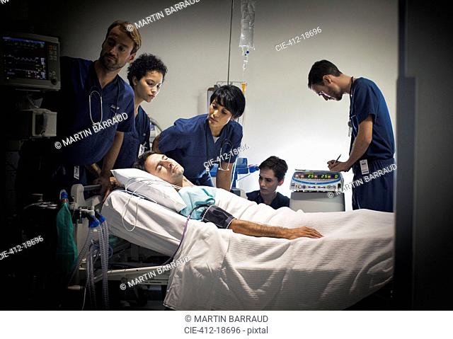 Group of doctors caring for patient in hospital ward