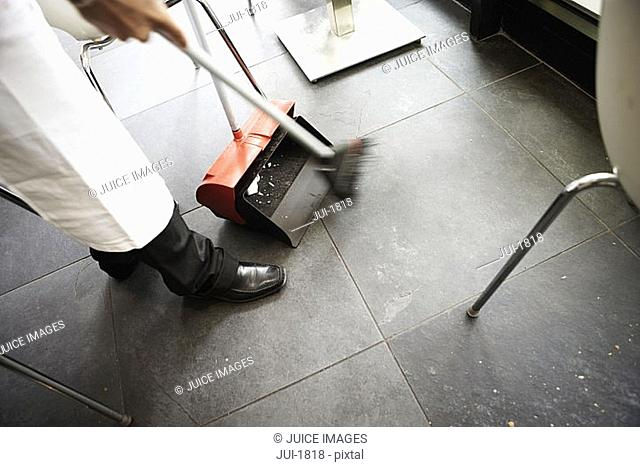 Waiter cleaning cafe floor with dustpan and brush, low section, side view tilt