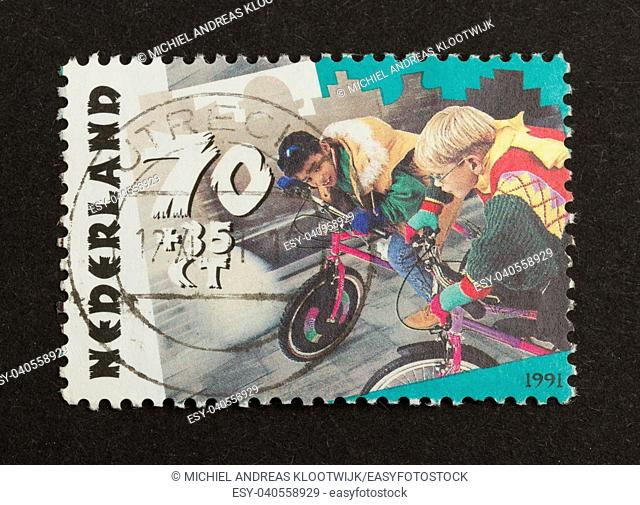 HOLLAND - CIRCA 1990: Stamp printed in the Netherlands shows two children racing on bikes, circa 1990
