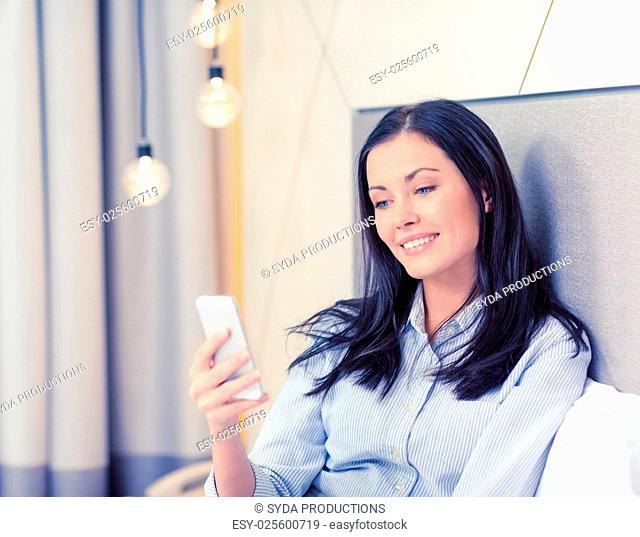 business, technology, internet and hotel concept - happy businesswoman with smartphone lying in hotel in bed