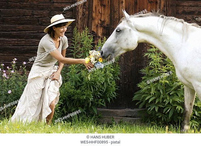Horse smelling at woman's bunch of flowers