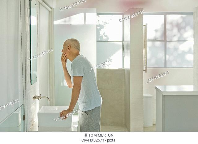Mature man touching face at bathroom mirror