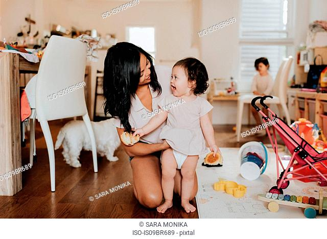Woman changing clothes on toddler daughter