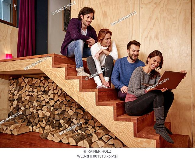 Friends sitting on wooden stairs using laptop