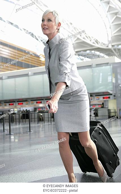 Mature woman pulling luggage in airport