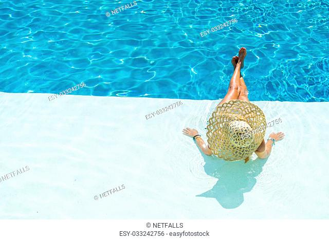 Young woman sitting on the ledge of the swimming pool