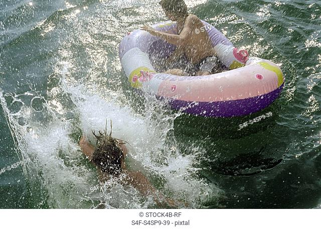 Boy in a Rubber Boat next to his Friend who jumped into the Water - Fun - Youth - Lake