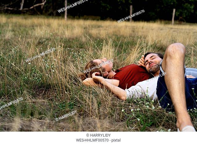 Happy couple cuddling, lying on a meadow
