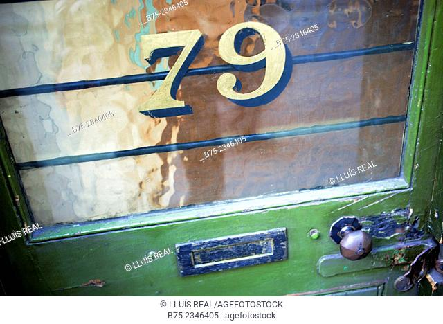 Number 79 in a green door of a shop with a latch and a letter box, in Beak street, Soho, London, England, UK, Europe