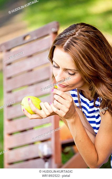 Woman with brown hair smelling flower while holding an apple