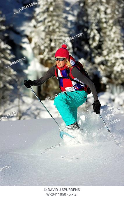 A women running through deep powders snow in snow shoes