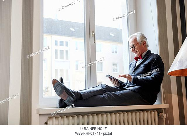 Senior man sitting in windowsill using tablet