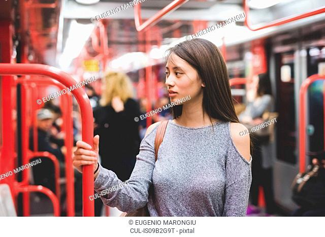 Young woman traveling on train carriage looking over her shoulder