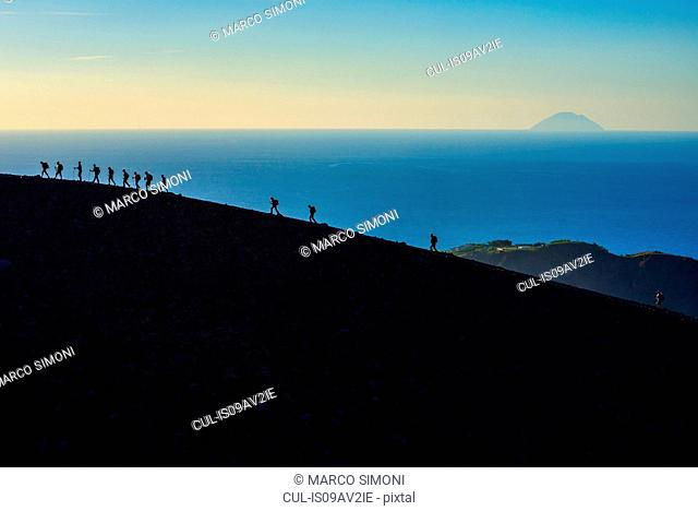 Large group of silhouetted tourists walking rim at Gran Cratere, Vulcano Island, Aeolian Islands, Sicily, Italy