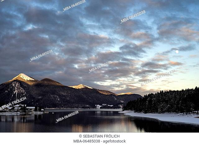 The Jochberg is shone on by the last evening light. Snow covers the village Walchensee and the shore of the Walchensee