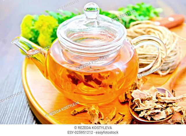 Herbal tea in a glass teapot from the root of Rhodiola rosea on a round tray, fresh flowers and dried root of Rhodiola rosea on the background of wooden boards