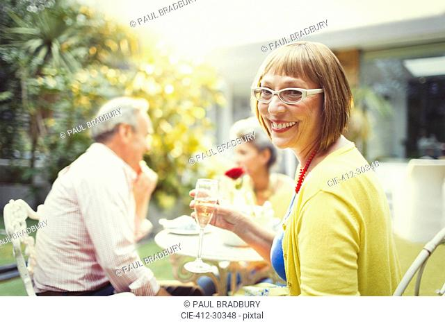 Portrait smiling woman drinking champagne at garden party
