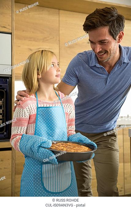 Girl carrying homemade gluten-free apple and almond cake for father in kitchen