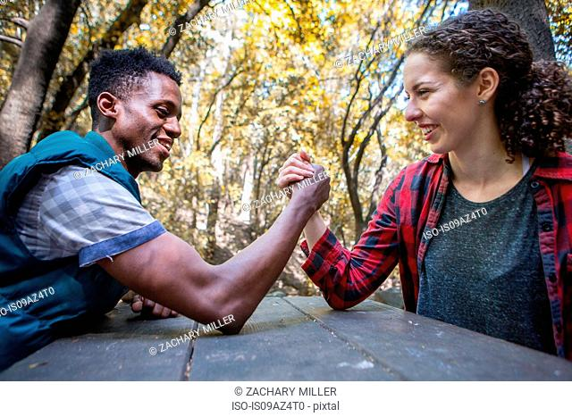 Young female hiker arm wrestling boyfriend at forest picnic table, Arcadia, California, USA