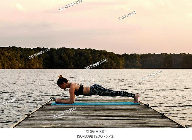 Side view of woman planking on pier by lake, North Carolina, USA