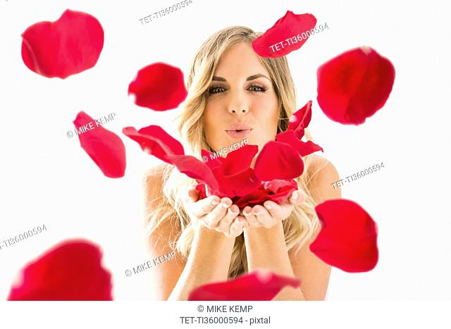 Young woman blowing rose petals off from hands