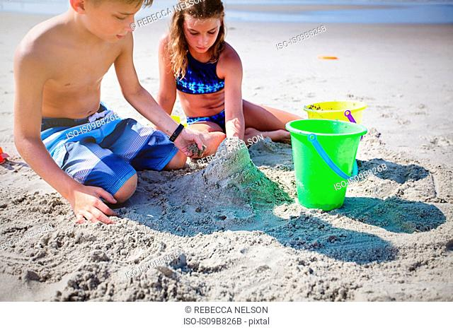 Siblings playing with sand on beach