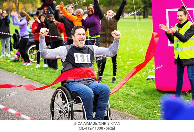 Enthusiastic man in wheelchair crossing finish line at charity race in park