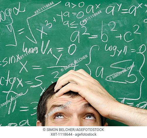 Confused Man in Front of Math Formula Written on a Chalkboard