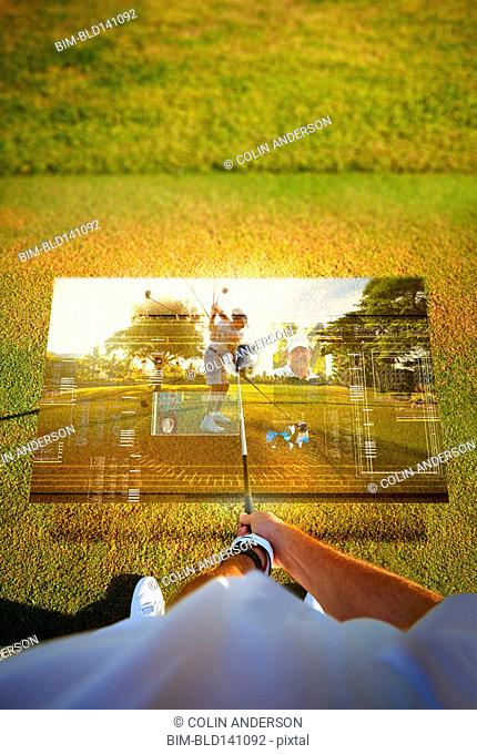 High angle view of Caucasian golfer holding club at ball over hologram
