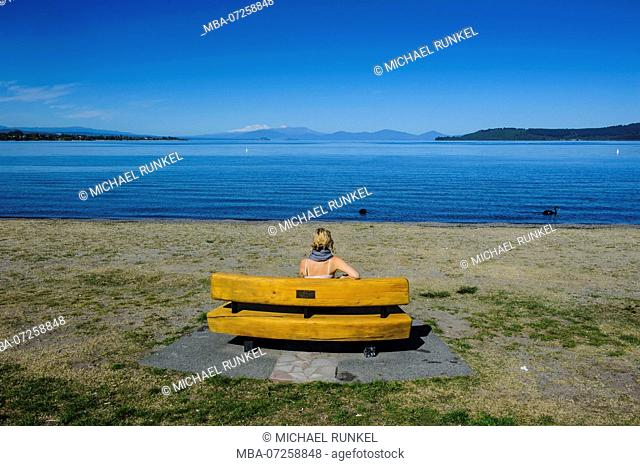 Woman sitting on a bench and enjoys the blue waters of Taupo lake with the Tongariro National Park in the background, North Island, New Zealand, MR