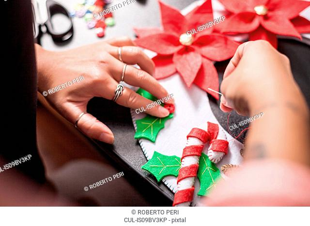 Over shoulder view of woman stitching holly berry onto christmas decoration, detail of hands
