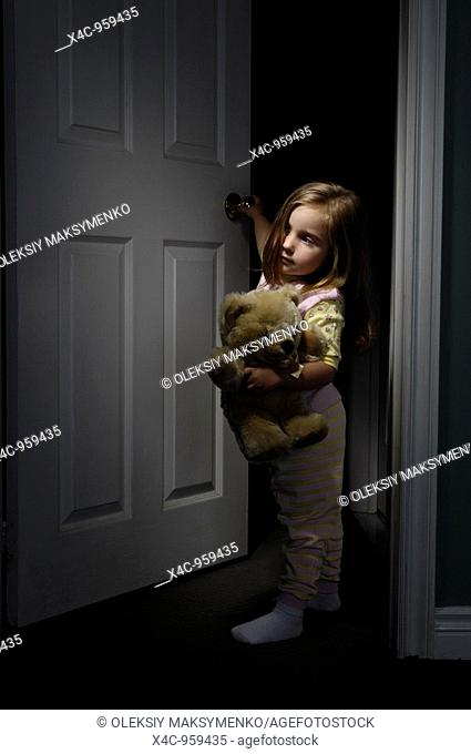 Little girl wearing pajamas and holding a teddy bear standing at the door and looking out of a room at night