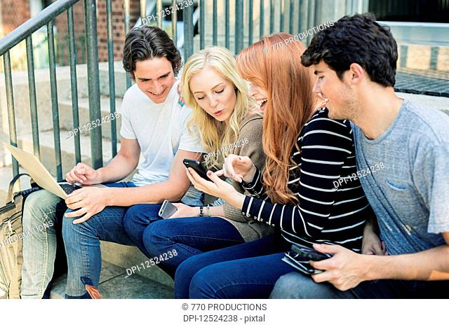 Four students sitting in a row on a step using their technology on the university campus and laughing together; Edmonton, Alberta, Canada