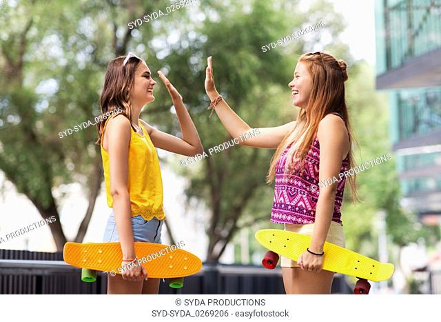 teenage girls with skateboards making high five