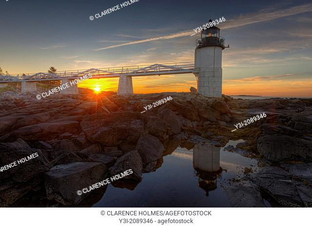 Marshall Point Lighthouse and its reflection in a tidal pool at sunrise in Port Clyde, Maine