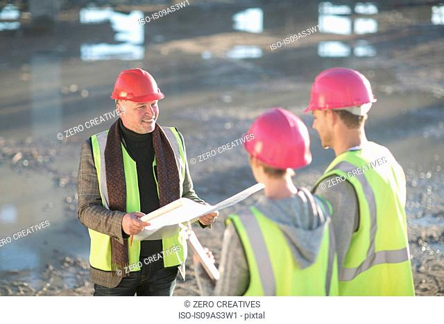 Architect meeting with builders on construction site