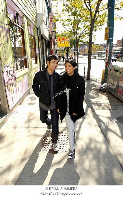 Young couple walking on Spadina Avenue, Toronto, Ontario