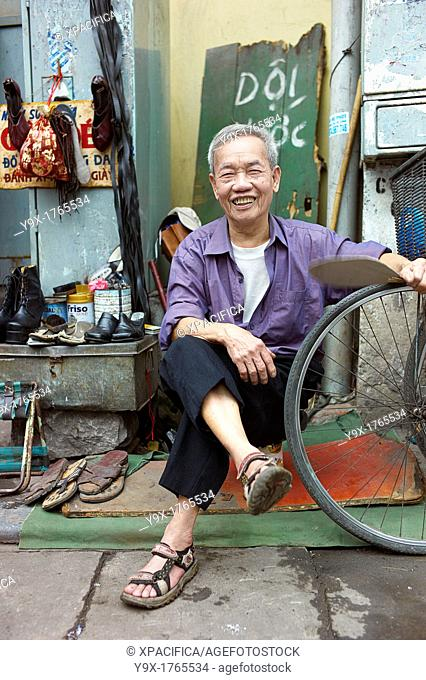 An old man on the side of the street who fixes old shoes