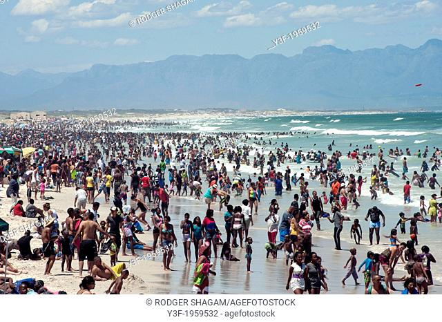 Crowds op people flock to the beach on a warm summer's day. New Year's Day. Cape Town, South Africa