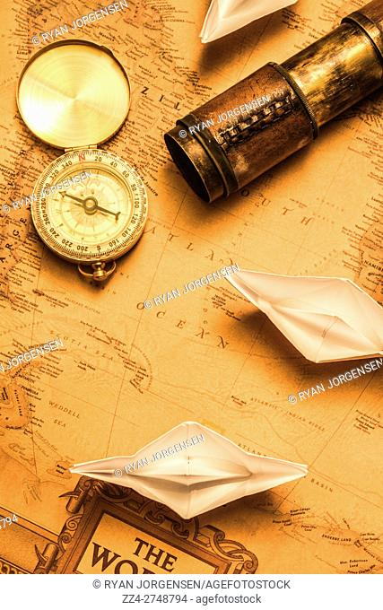 Origami paper boats on a voyage of exploration viewed from above on an ancient chart of the world with vintage brass compass and telescope for navigating the...