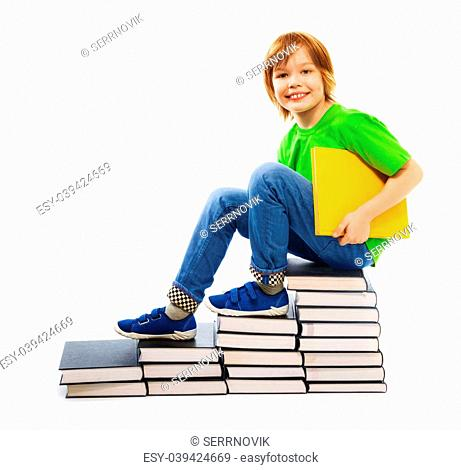 Happy Caucasian 9 years old boy in green shirt standing on stairs made of stack of books holding yellow hardcover book, isolated on white